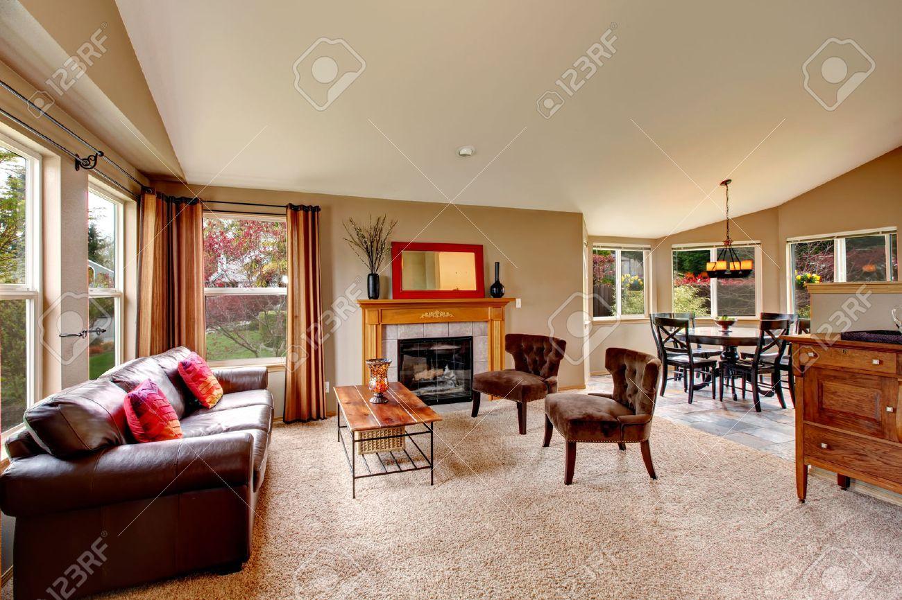 Lichte woonkamer met beige vloerbedekking, leren bank, salontafel ...