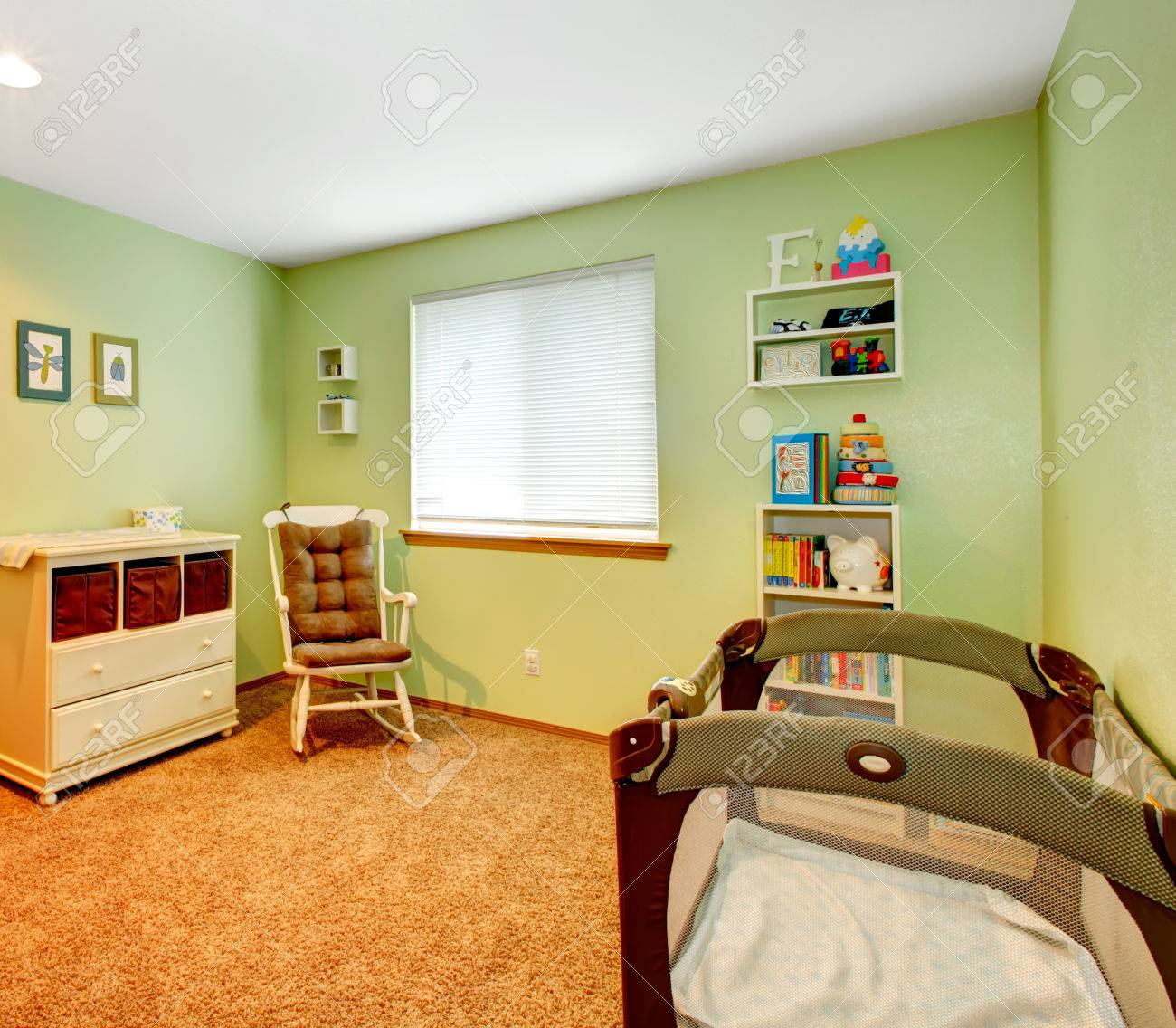 Baby cribs green - Green And Beige Cozy Nursery Room With Baby Crib Rocking Chair And Wooden Cabinet Stock