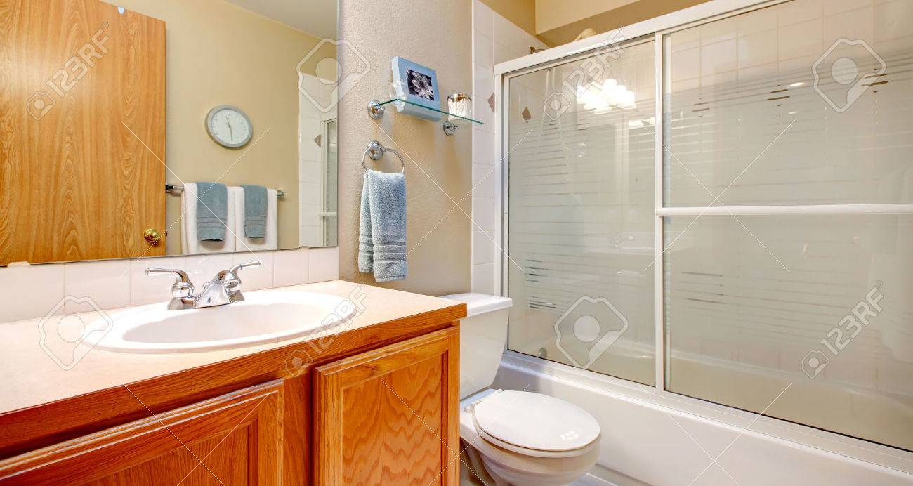 Light Tones Bathroom With Wooden Washbasin Cabinet, White Tub With Glass  Sliding Doors Stock Photo
