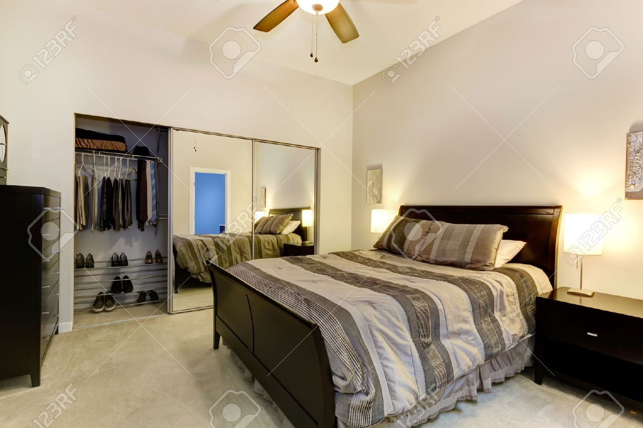 elegant bedroom with dark brown furniture, mirror door closet