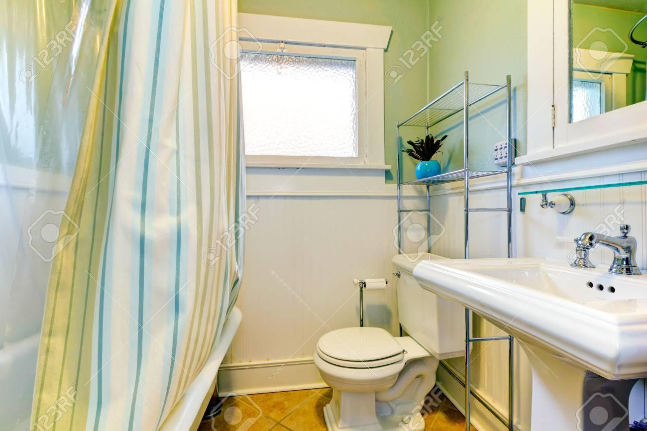Salle de bains lumineuse avec fenêtre. Mur vert et blanc correspond à  rideaux verts rayés.
