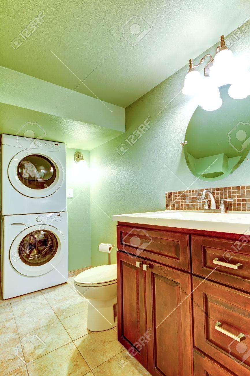 Bois Salle De Bain salle de bains avec des carreaux vert-de-chaussée beige, meuble vasque en  bois. salle de bain a une buanderie avec lave-linge et sèche-linge