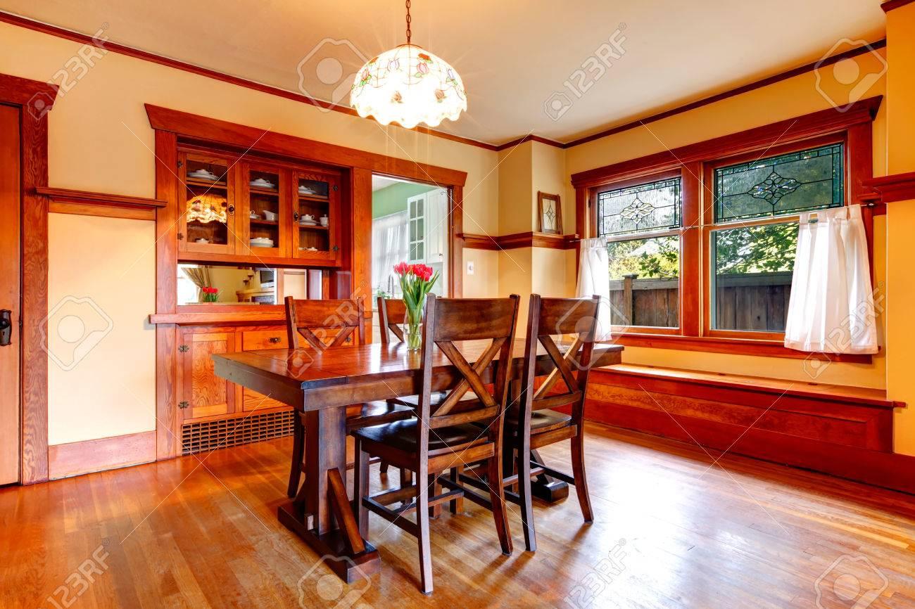 Brillante comedor con juego de mesa de comedor rústico, armarios  empotrados. Mesa decorada con flores frescas.