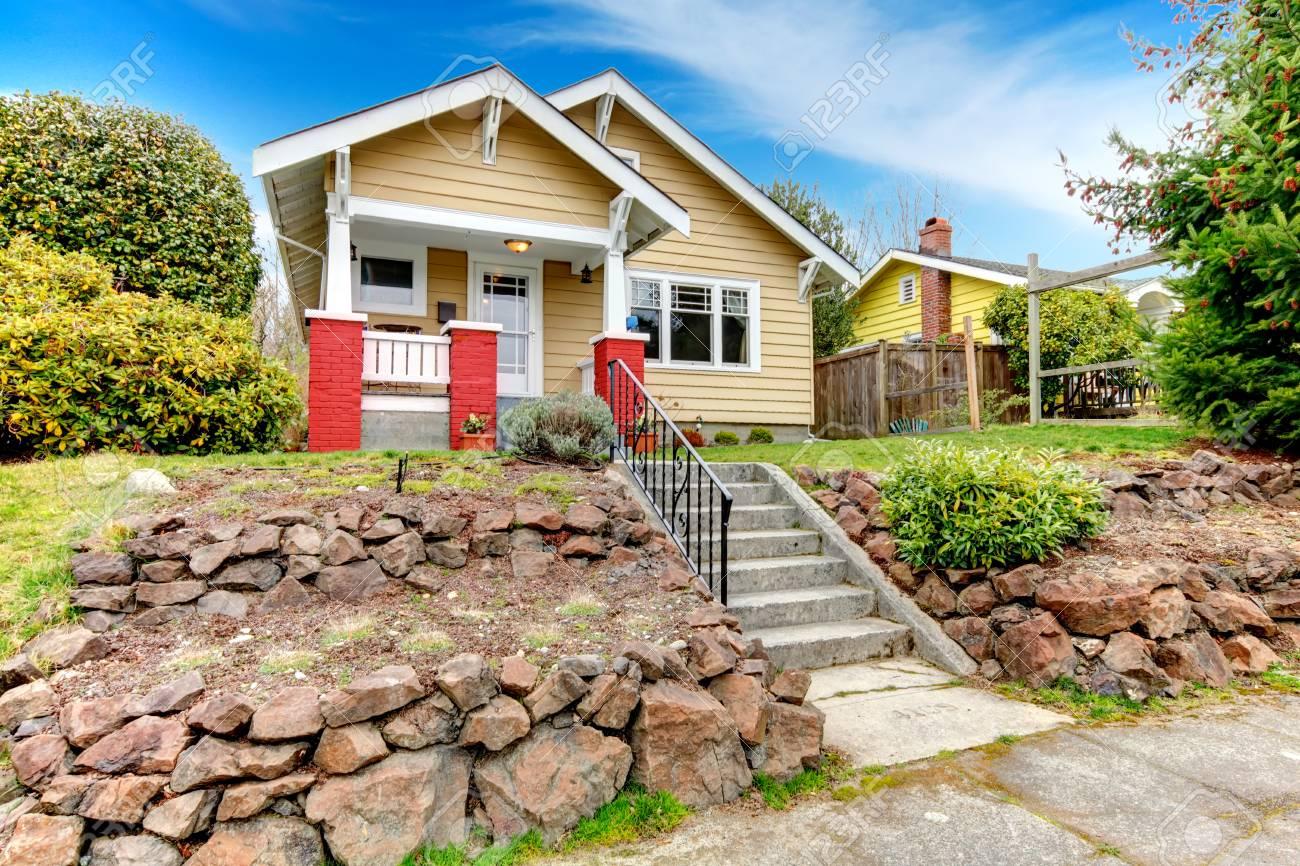 Bardeau maison de bardage avec terrasse aménagement paysager. Porche à  colonnes de base de brique
