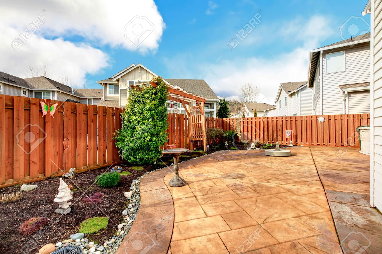 fenced backyard with concrete tile floor deck and decorated flower bed stock photo 26094535