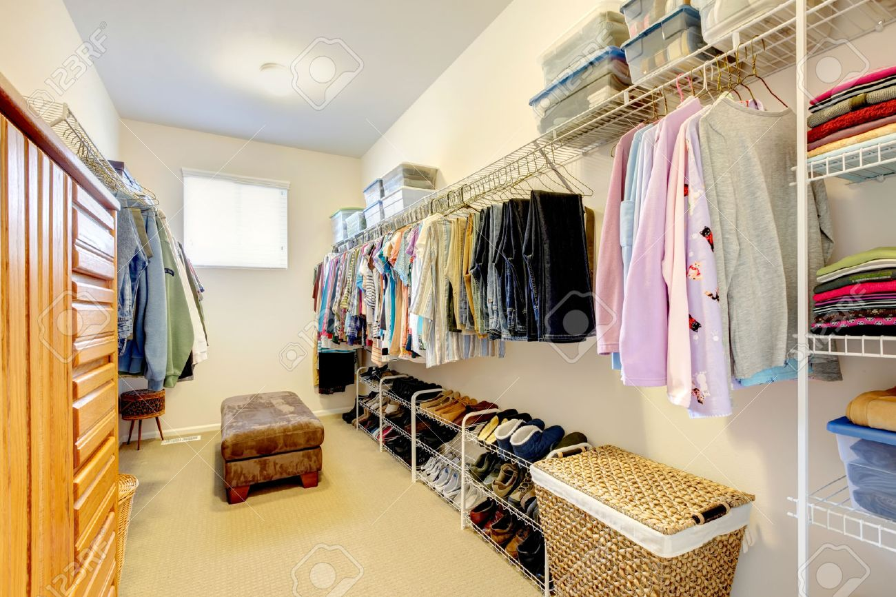 Grande cabina armadio con ripiani per i vestiti e le scarpe, comò e cesti  di vimini
