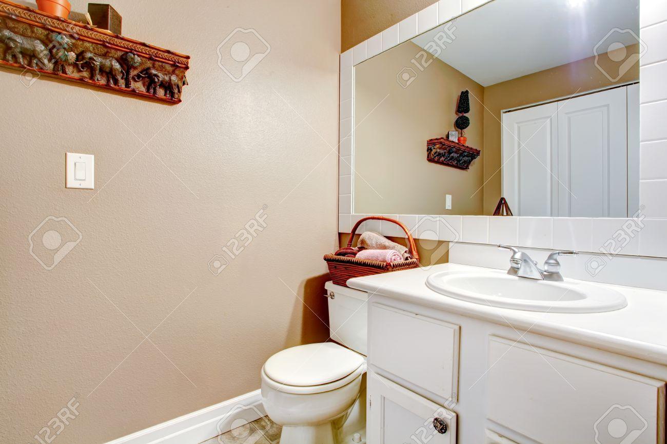 Salle de bains de mur beige avec du blanc lavabo en bois, avec WC. Décoré  avec une serviette de panier en osier et étagère murale en bois