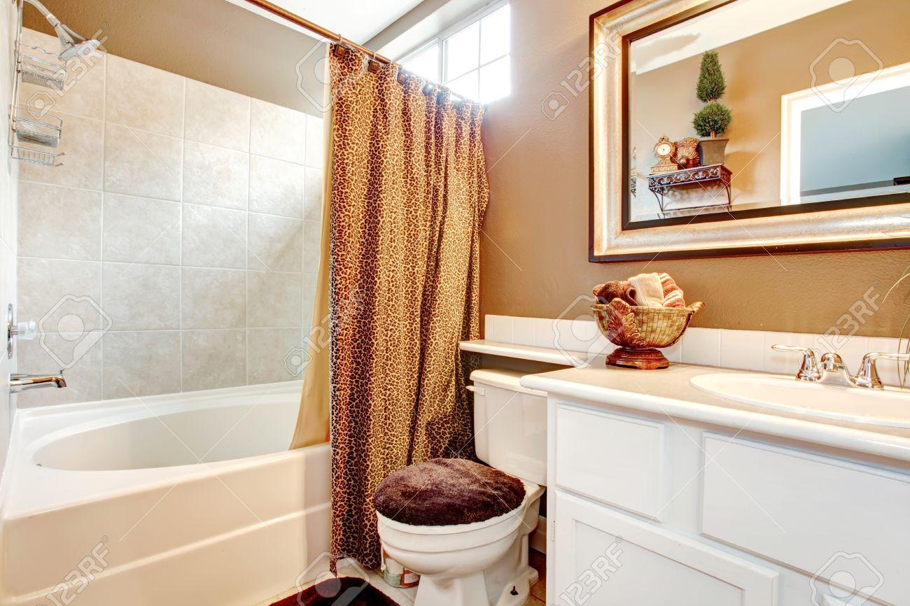 Salle de bains de mur beige avec meuble vasque blanc, miroir ...