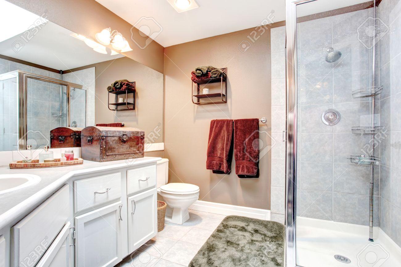 Beige et salle de bains avec douche blanche de porte en verre, carrelage et  tapis vert tendre. Décoré avec une serviette de Bourgogne, coffre ancien ...