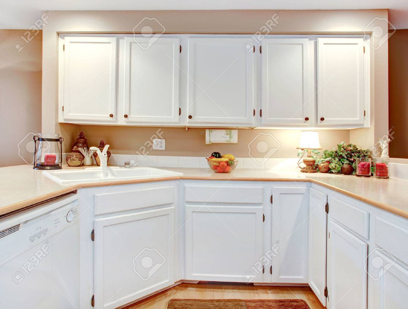 Bright Kitchen With White Wooden Cabinets And Beige Counter Tops