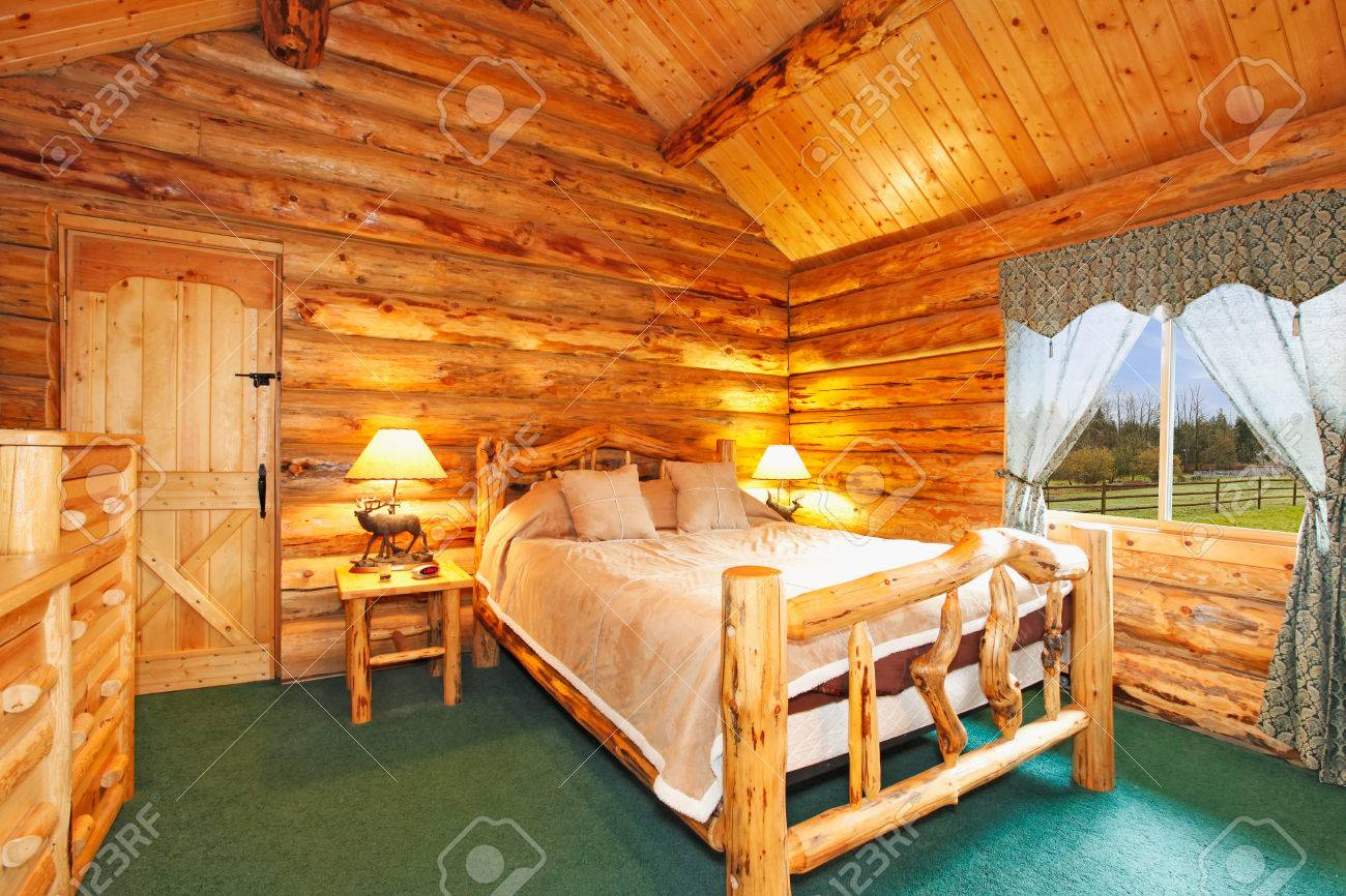 Cozy bedroom at night - Stock Photo Warm Cozy Bedroom With Rustic Bed Nightstand And Dresser Green Carpet Floor And Curtains Log Cabin House Interior