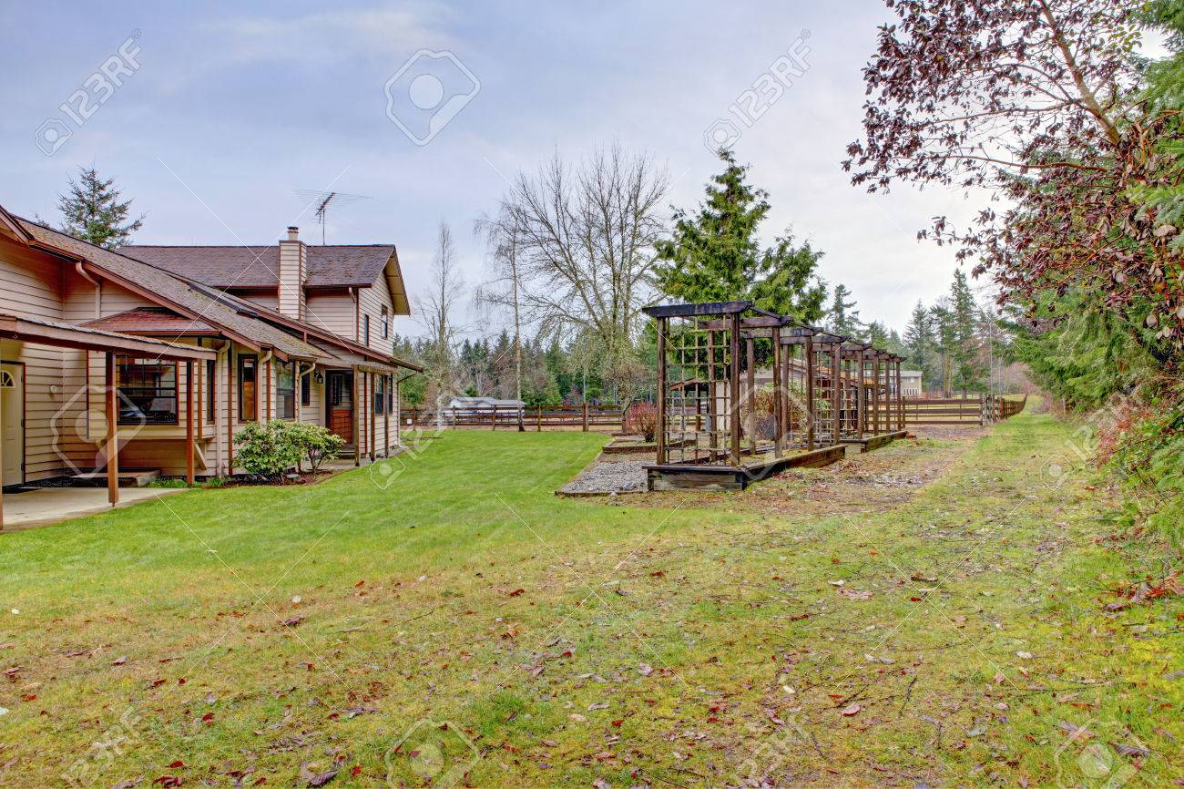 farm house backyard wigh a lawn trees and wooden grids view