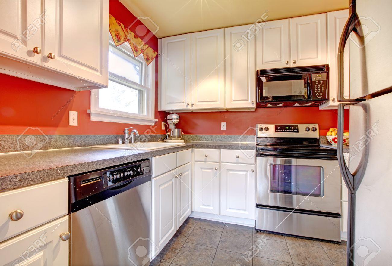 Piccola cucina abitabile con pavimento in cemento piastrelle, pareti rosse,  elettrodomestici in acciaio e legno, armadi bianchi
