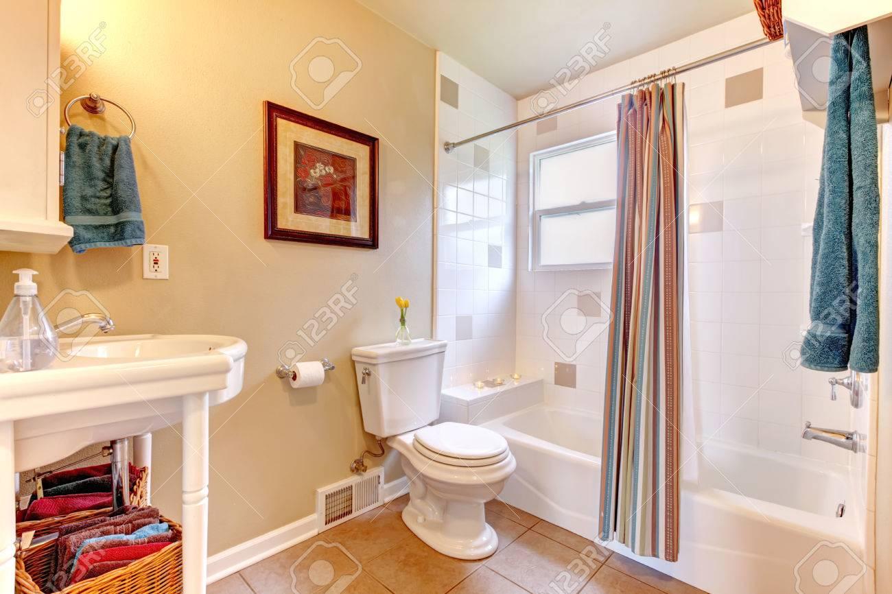Salle de bain blanc et ivoire lumineux avec carrelage beige. Baignoire  blanche ornée de rideaux rayés