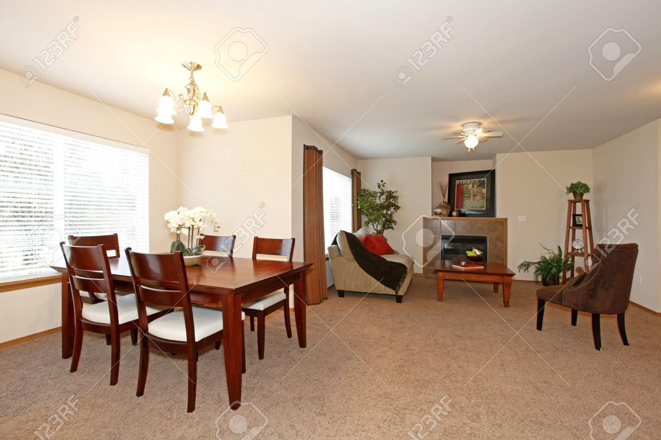 Paredes ligeras de estar y comedor con piso de alfombra marrón. Amueblado  con juego de mesa de comedor, una silla y un sofá. Vista de la sala de ...