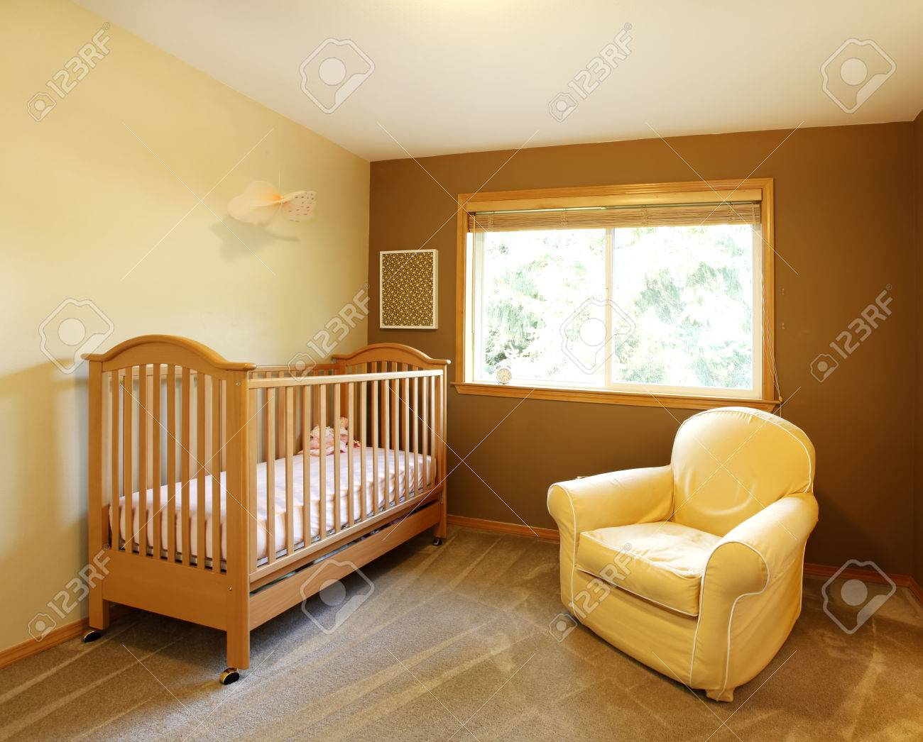 Chambre bébé avec lit et chaise murs jaune et brun.