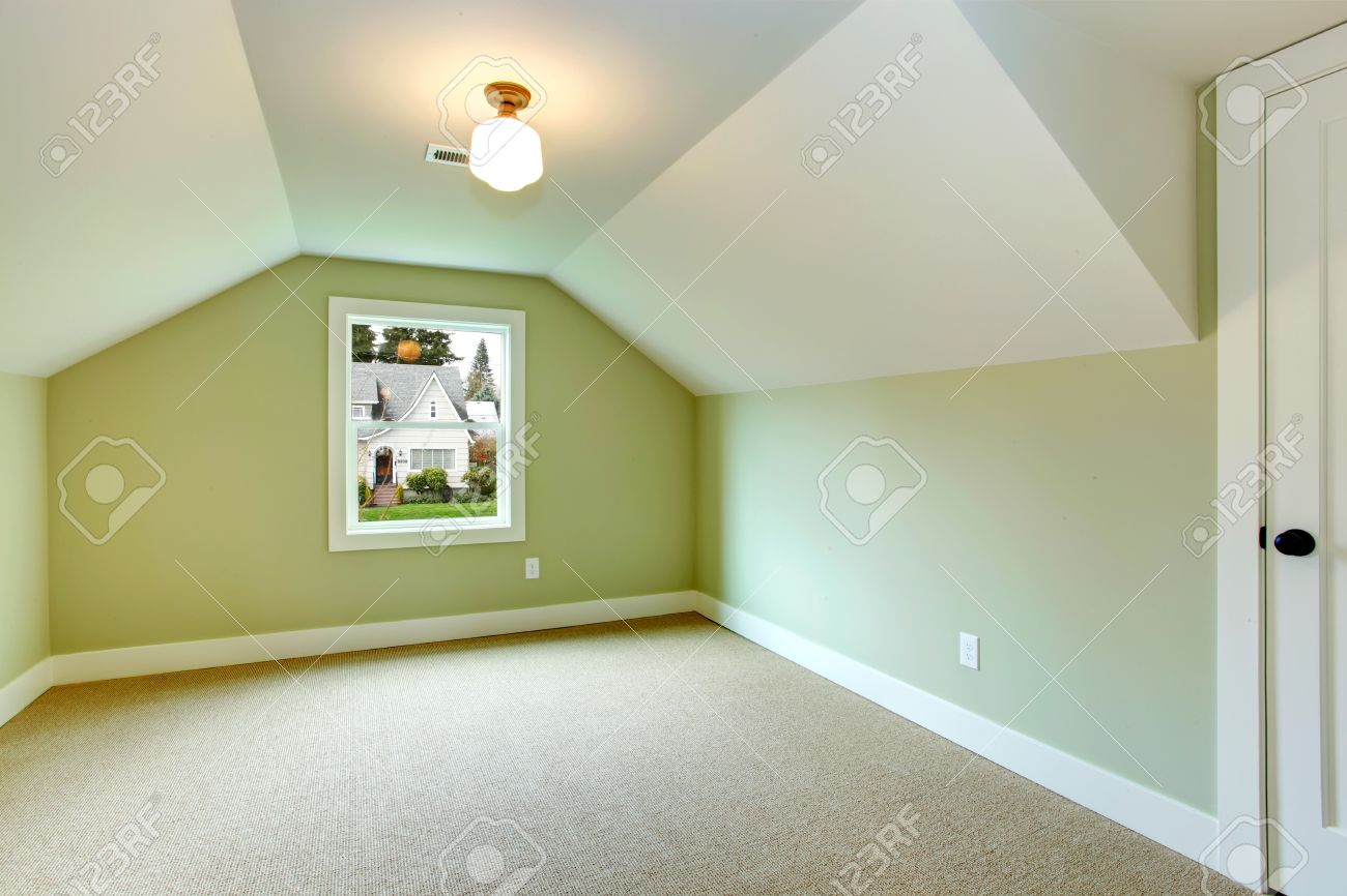 white carpet floor. bright empty room with one window, beige carpet floor, green walls and white vaulted floor