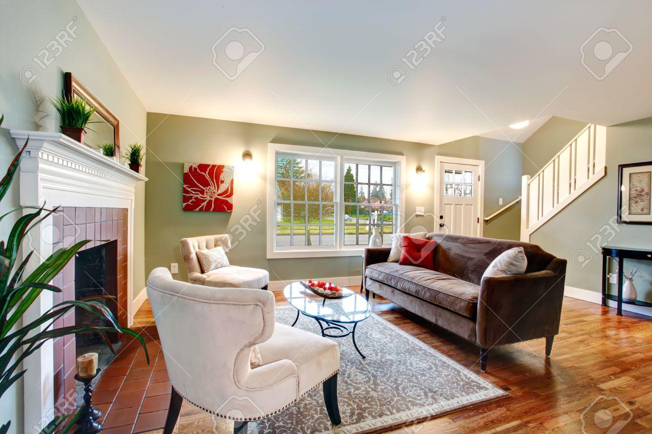 Verfrissende woonkamer met licht groene muren, houten vloer en wit ...