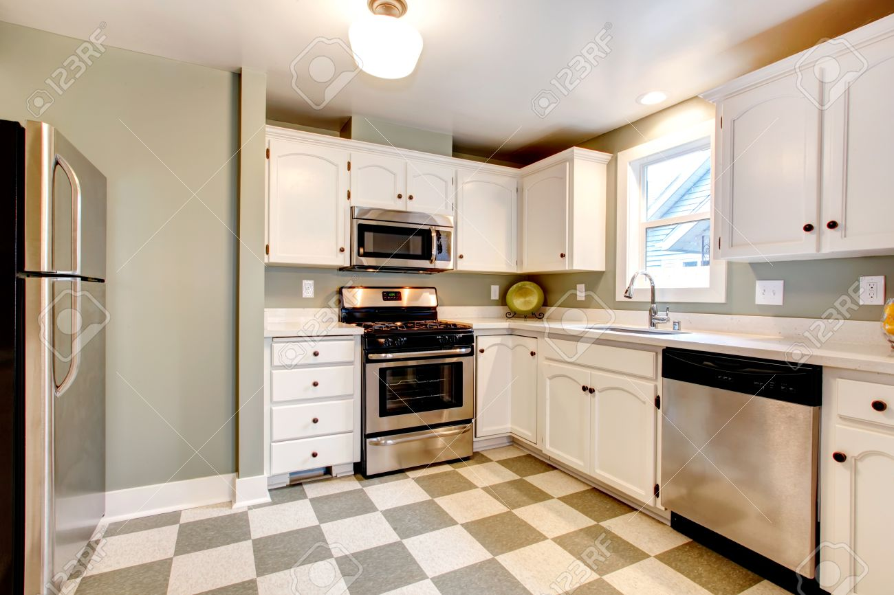 26450869 White kitchen cabinets blends perfectly with light olive walls olive and beige ceramic tile floor  Stock Photo