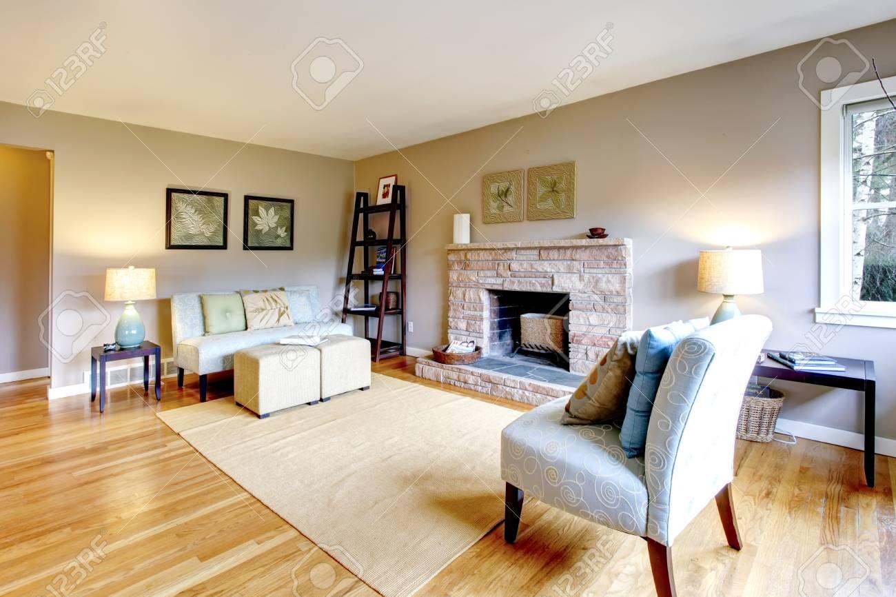 Salon lumineux avec un plancher de bois franc et rocheux cheminée en  arrière-plan. Meublé avec canapé classique et une chaise, une table et une  ...