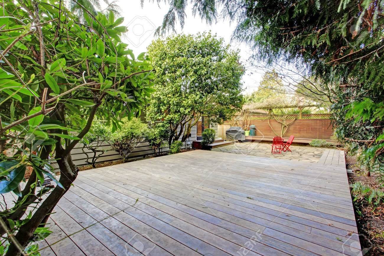Big Wooden Deck Surrounded By Green Trees. View Of A Small Patio Area. Stock