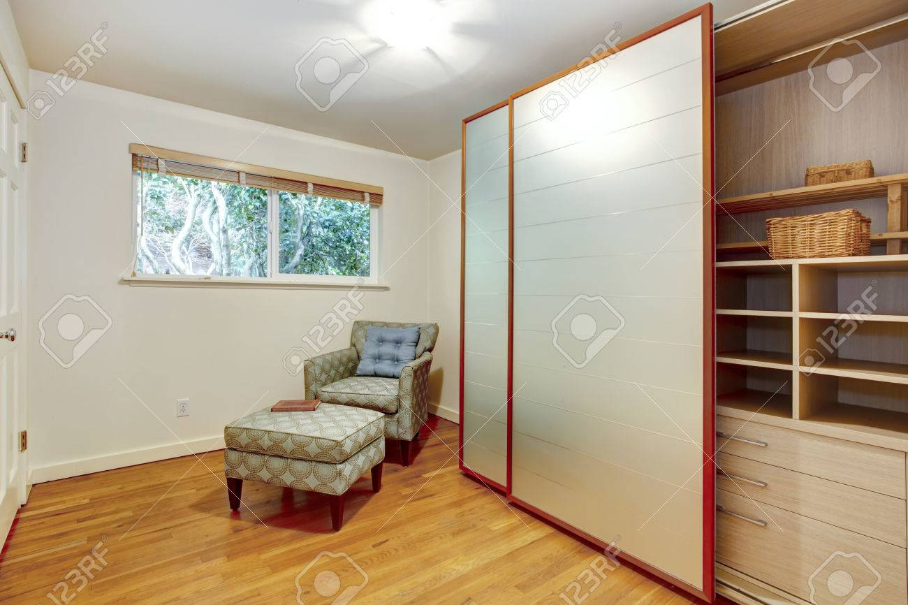 View Of The Room Corner With Chair And Open Slide Doors Wardrobe