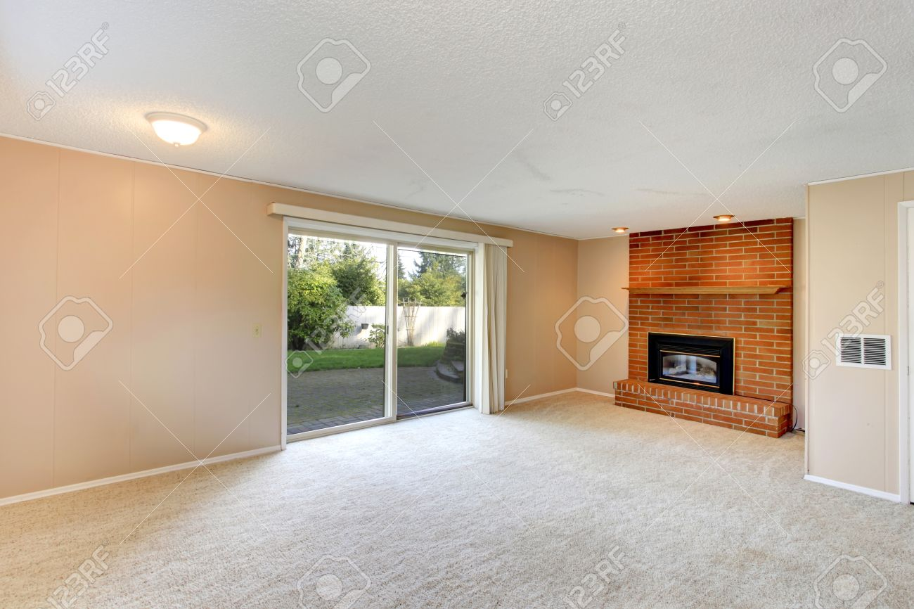 Empty Living Room With A Brick Background Fireplace Carpet Floor And Walkout Deck Stock Photo