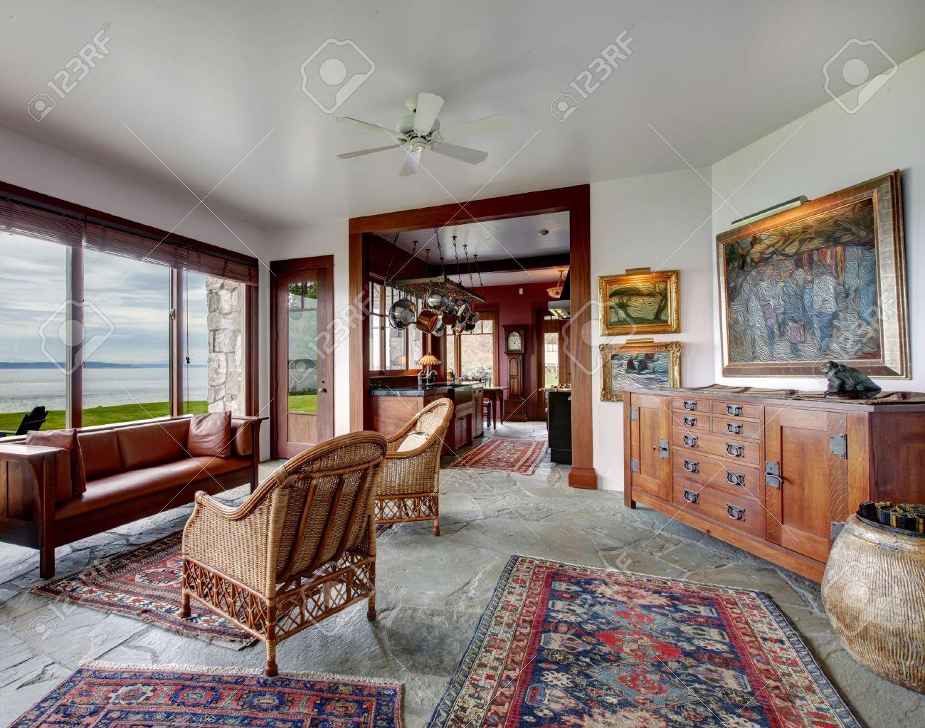 Ruime woonkamer met stenen vloer. ingericht met rieten antieke ...