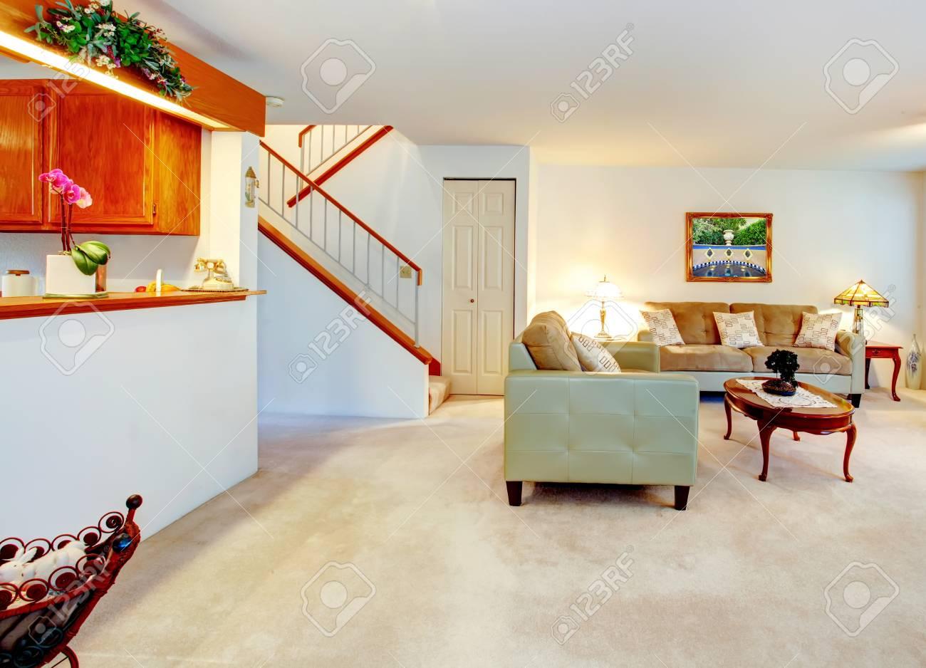 Salon lumineux avec une cheminée et meubles anciens. Vue de l\'escalier et  la cuisine mur ouvert.