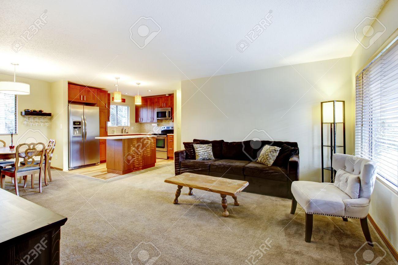 pared light salón con piso de alfombra beige, marrón sofá, silla