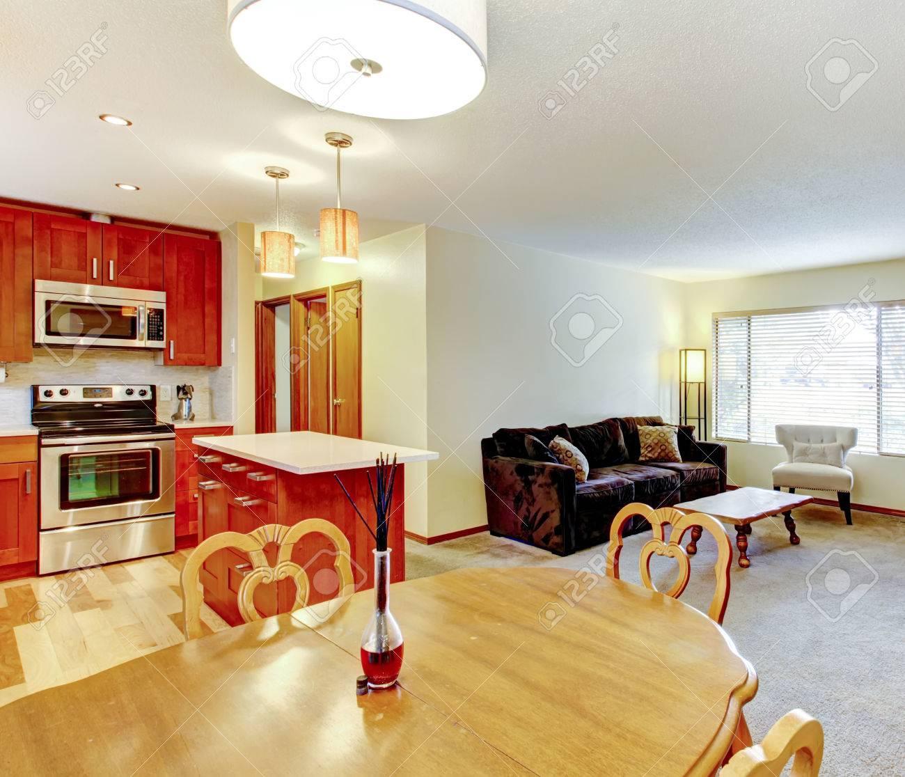 Lichte muur woonkamer met beige vloerbedekking, bruine bank ...