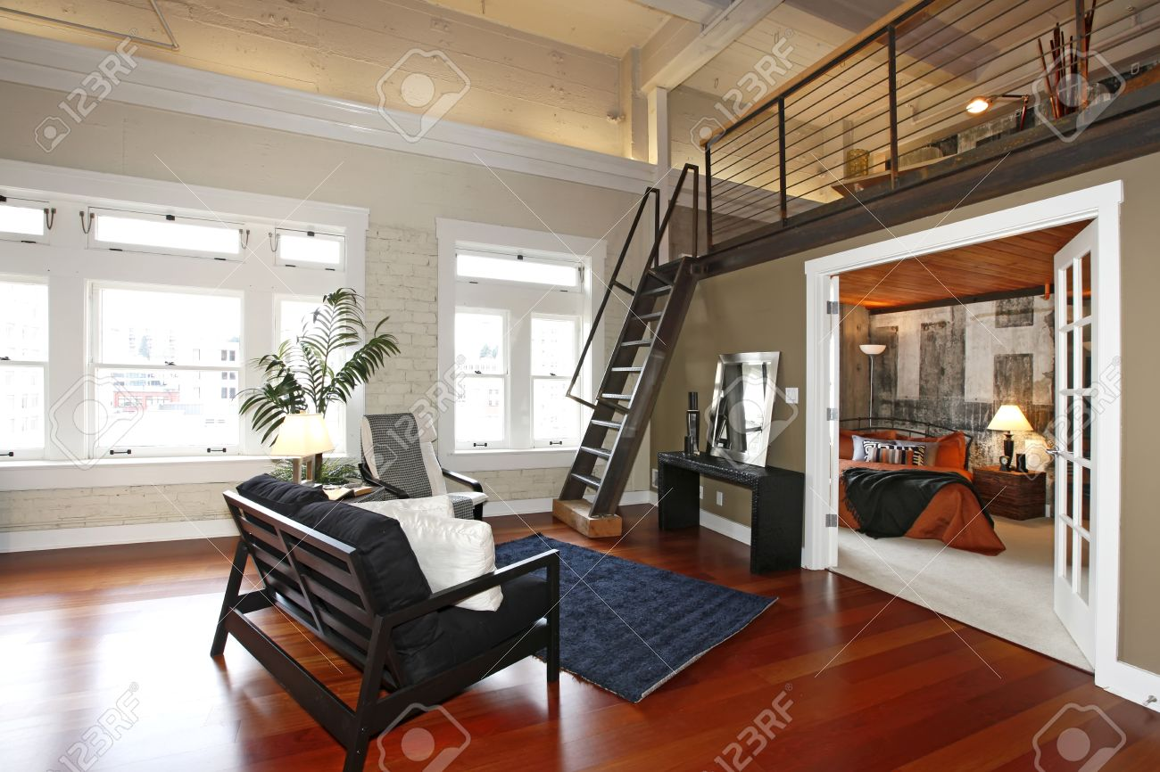 Modern Living Room With Brick Painted Wall, Hardwood Floor And Iron Steep  Stairs. View