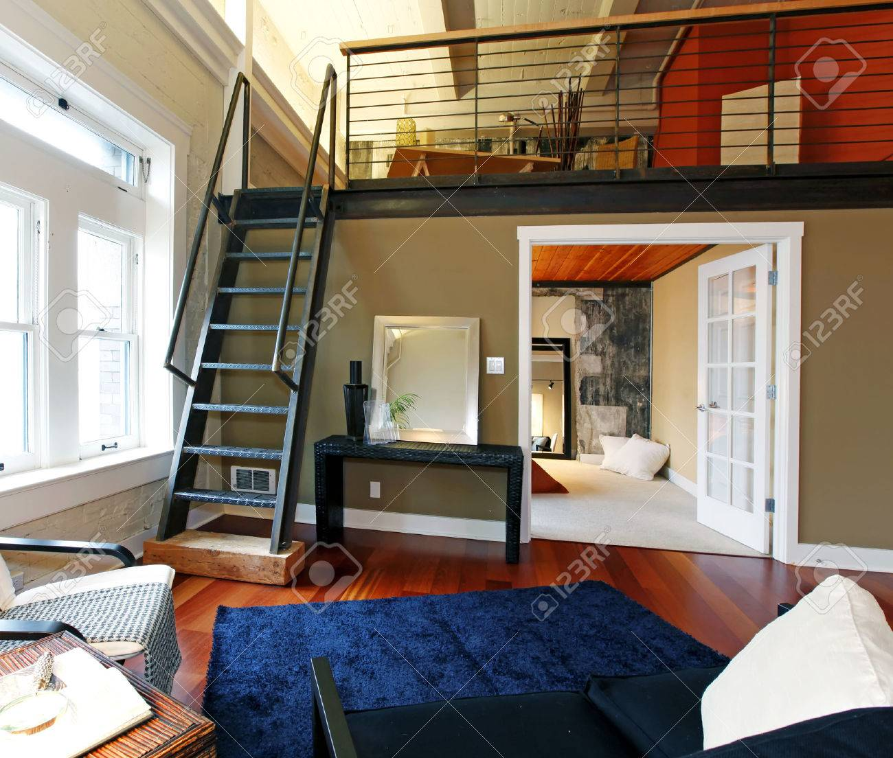 View of modern reconstructed living room with mezzanine area above bedroom.  View of iron steep