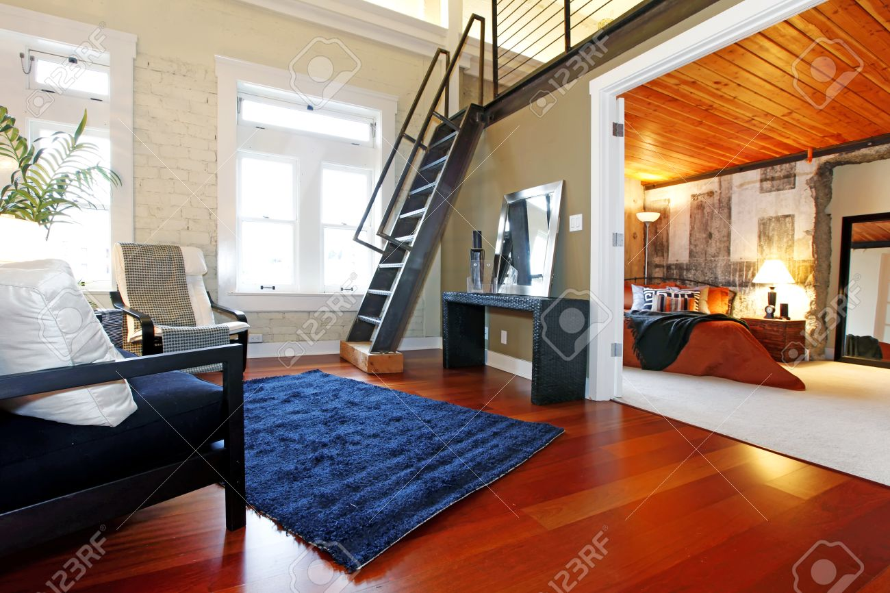 Salon moderne avec mur de briques peint, plancher de bois franc et ...