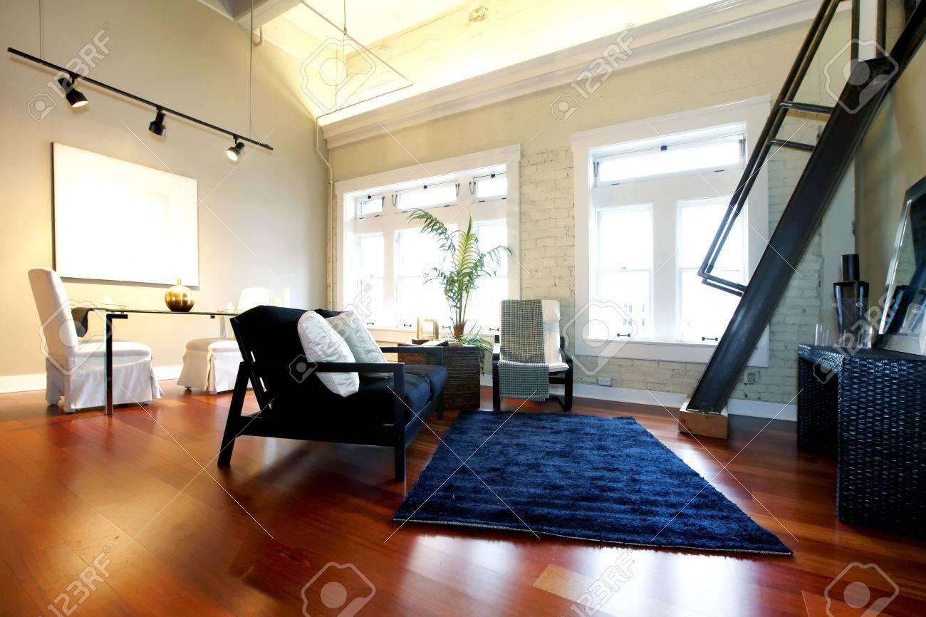 Salon moderne avec mur de briques peint, plafond haut, plancher de ...