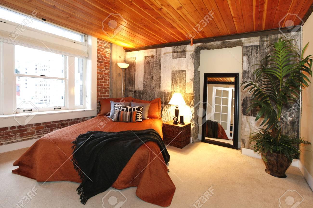Moderne slaapkamer met bakstenen bekleding, beton gebroken muur en ...