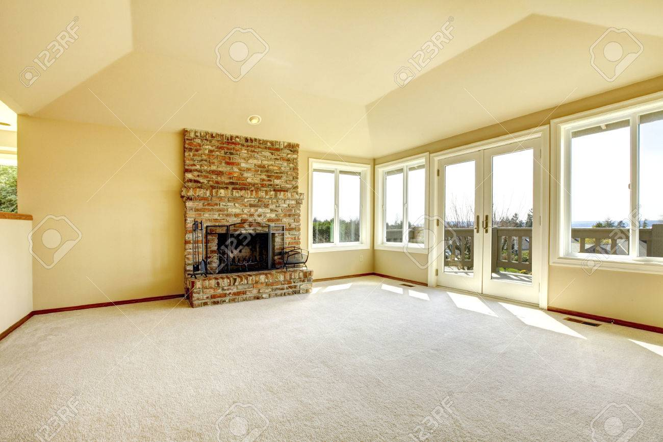 Bright Empty Living Room With High Vaulted Ceiling And Carpet Floor View Of Brick Background