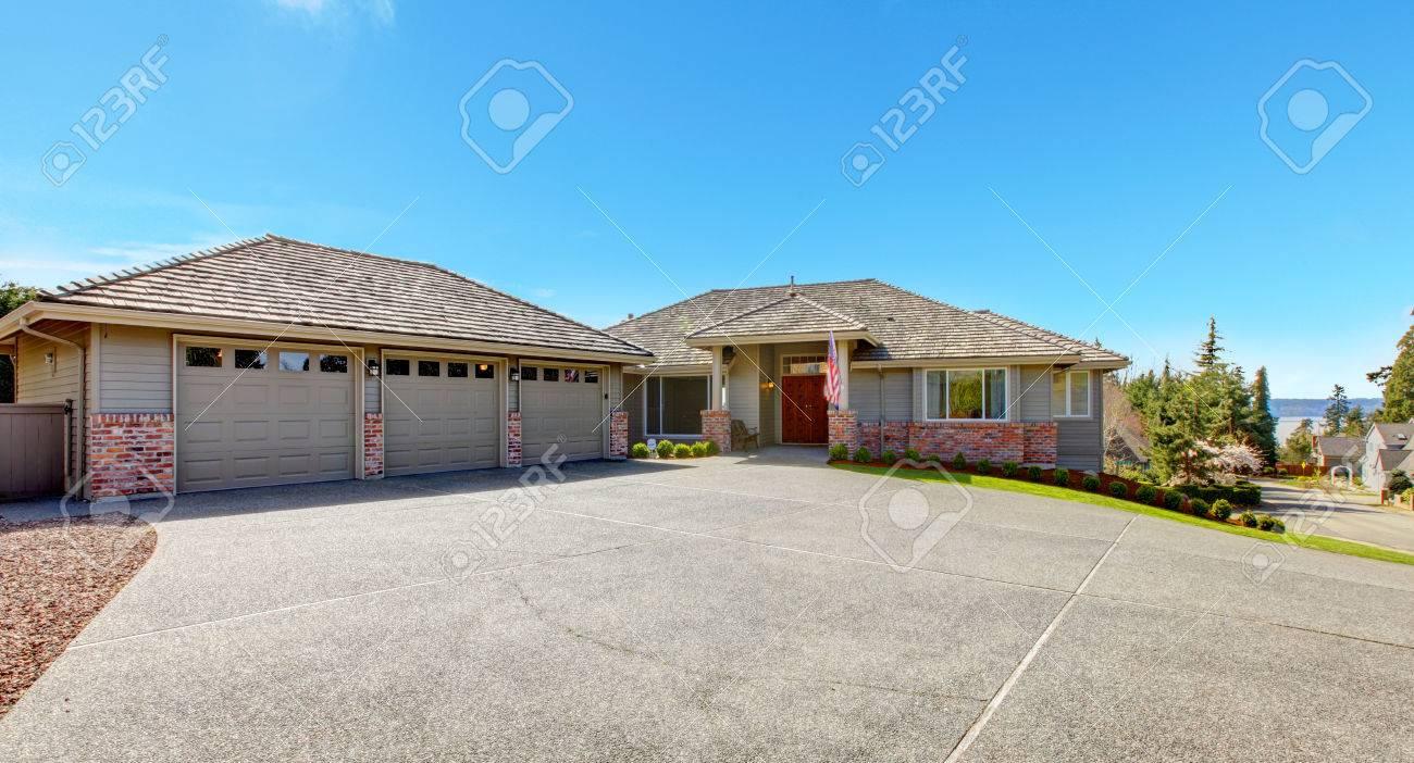 casa con pared de ladrillo guarnecido y porche de columnas vista de garaje para