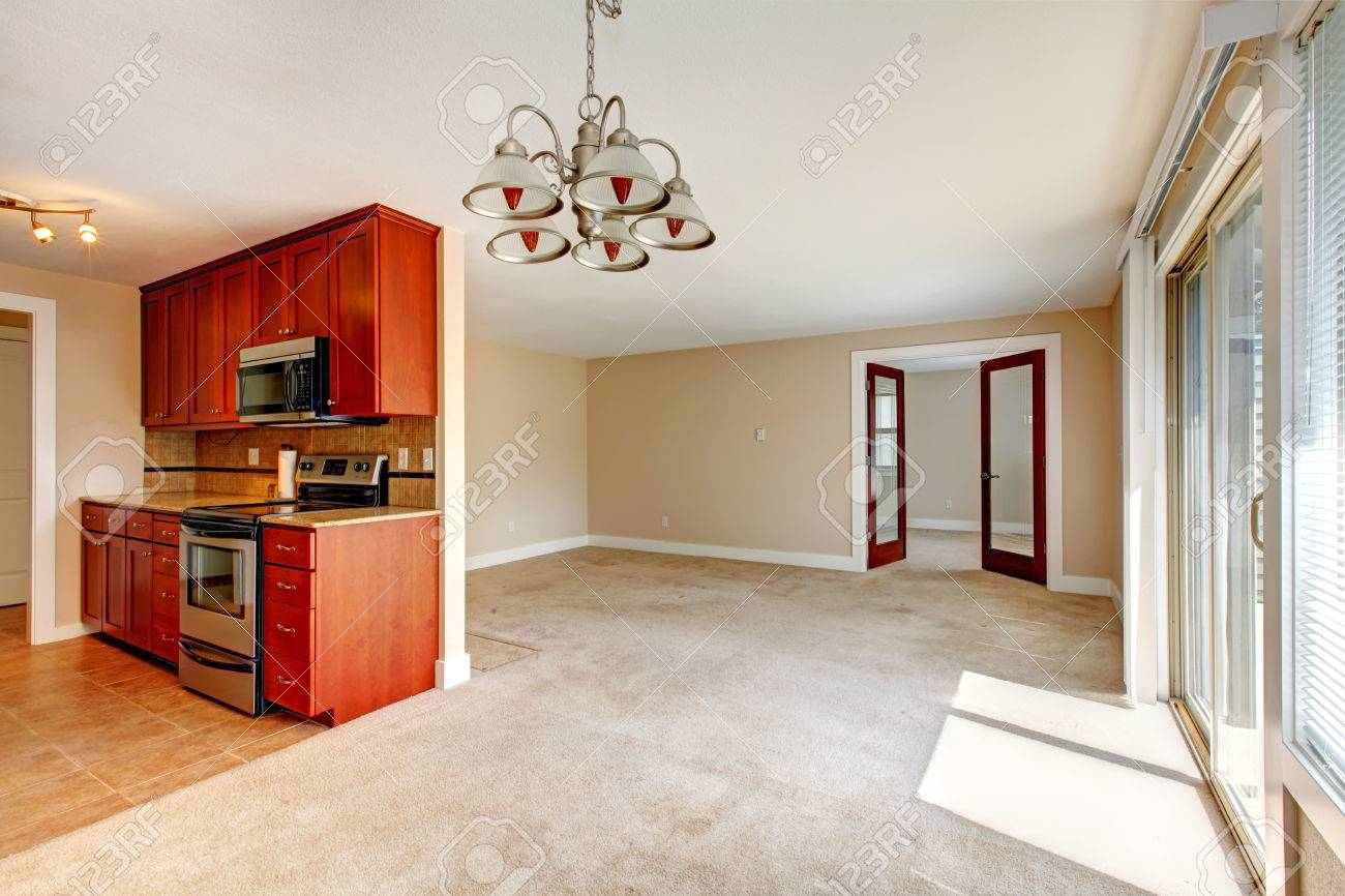 Empty living room with carpet - Empty Bright Living Room With Carpet Floor View Of Small Kitchen Area With Wooden Cabinets And