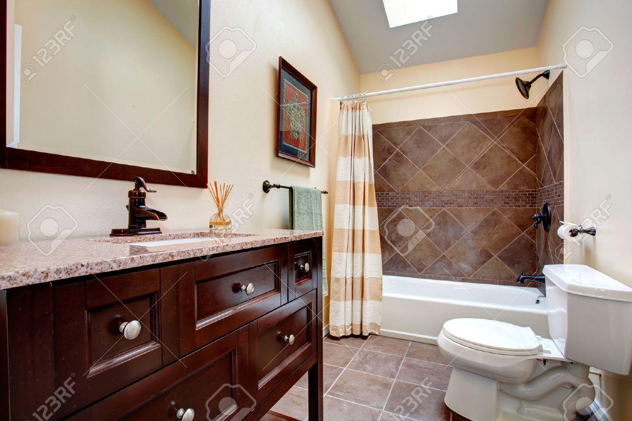 Salle de bains d\'Ivoire avec la couleur de chocolat vanité, toilette  blanche, baignoire avec garniture de carreaux de mur et rideau plissé