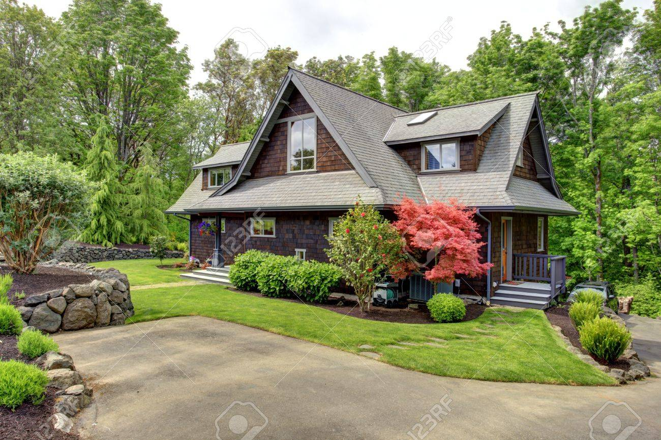 Clapbord Siding Brown House With Green Lawn And Amazing Blooming Trees View From The Driveway Stock