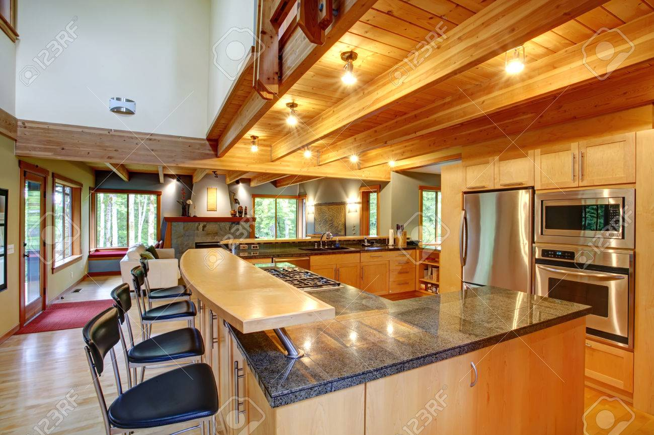 View of kitchen back with black high stools, steel appliances and ceiling beams Stock Photo - 27177080
