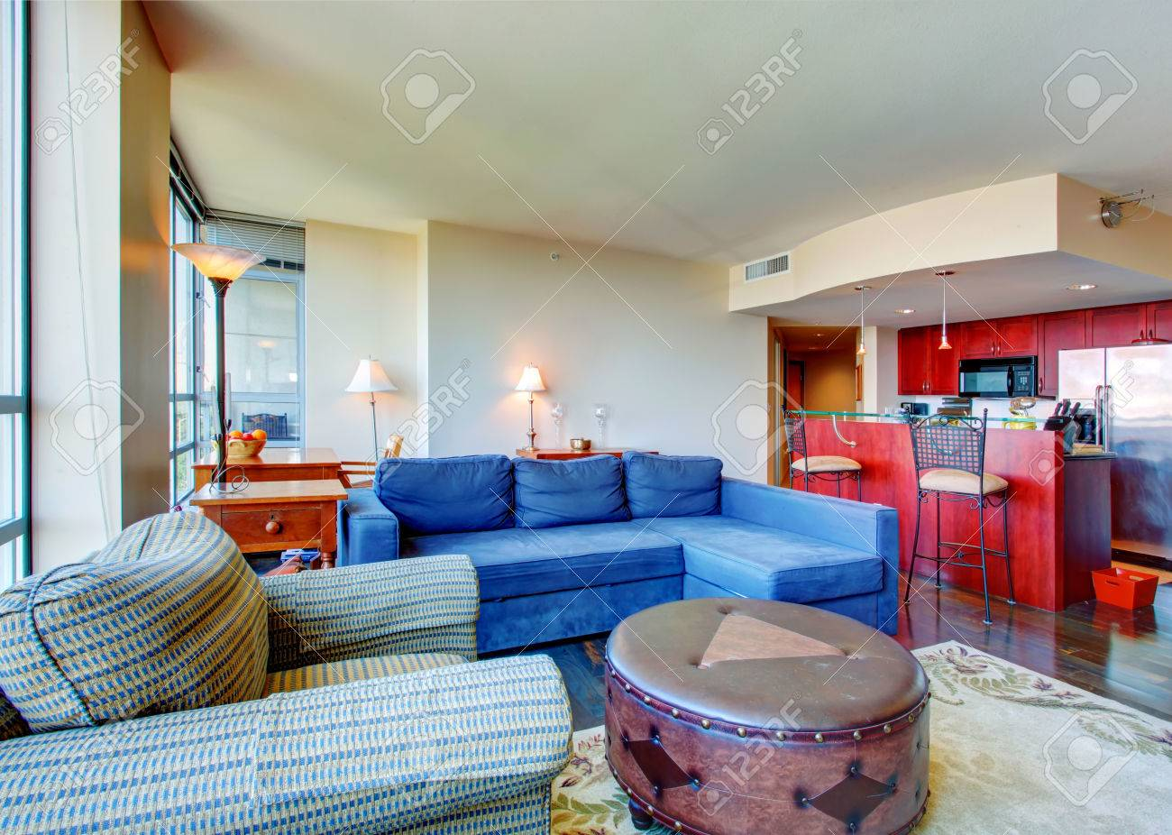 Living Room With Blue Sofa Striped Armchair And Leather Ottoman