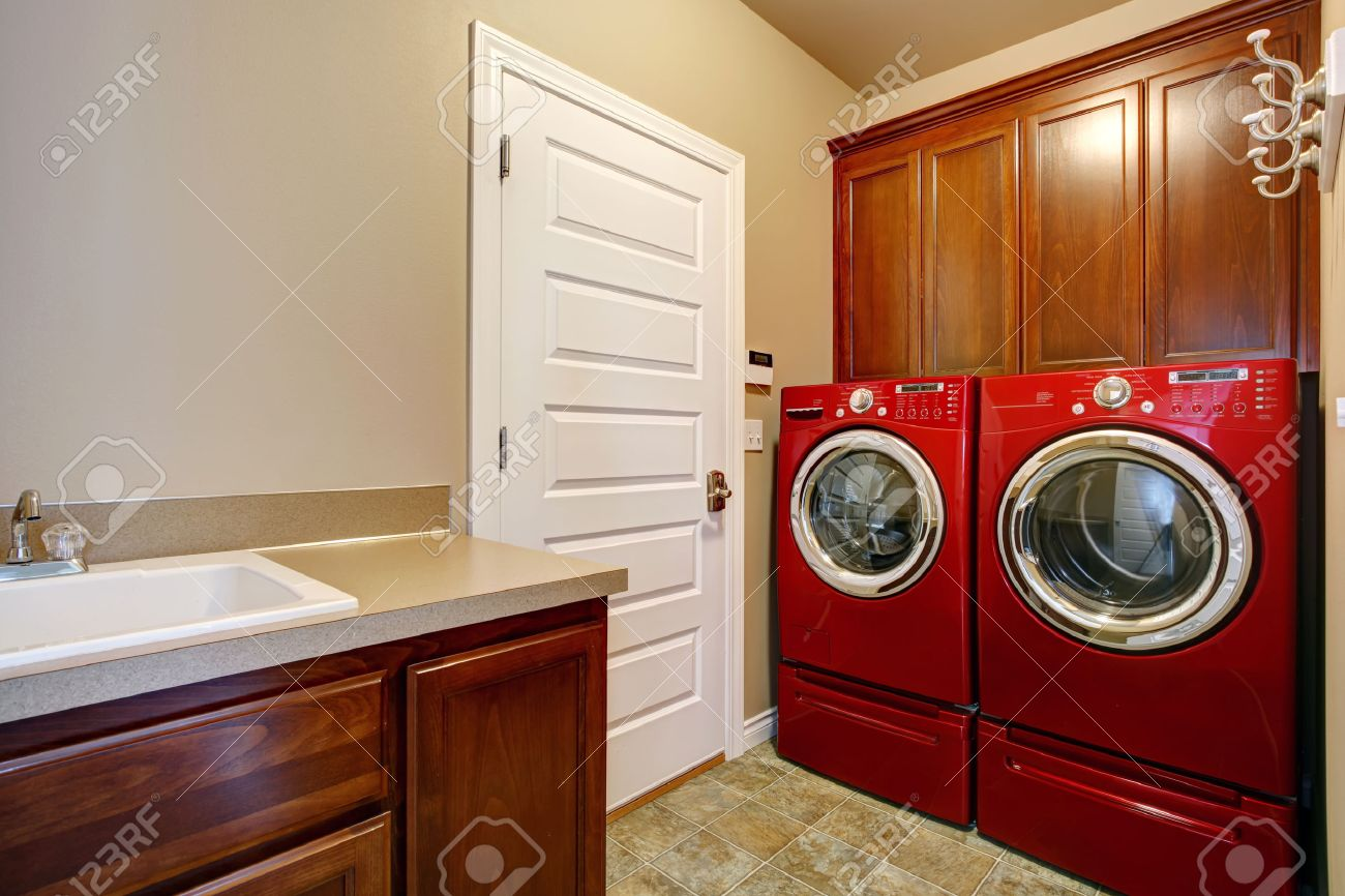 laundry room with wooden storage cabinets modern red washer and dryer stock photo