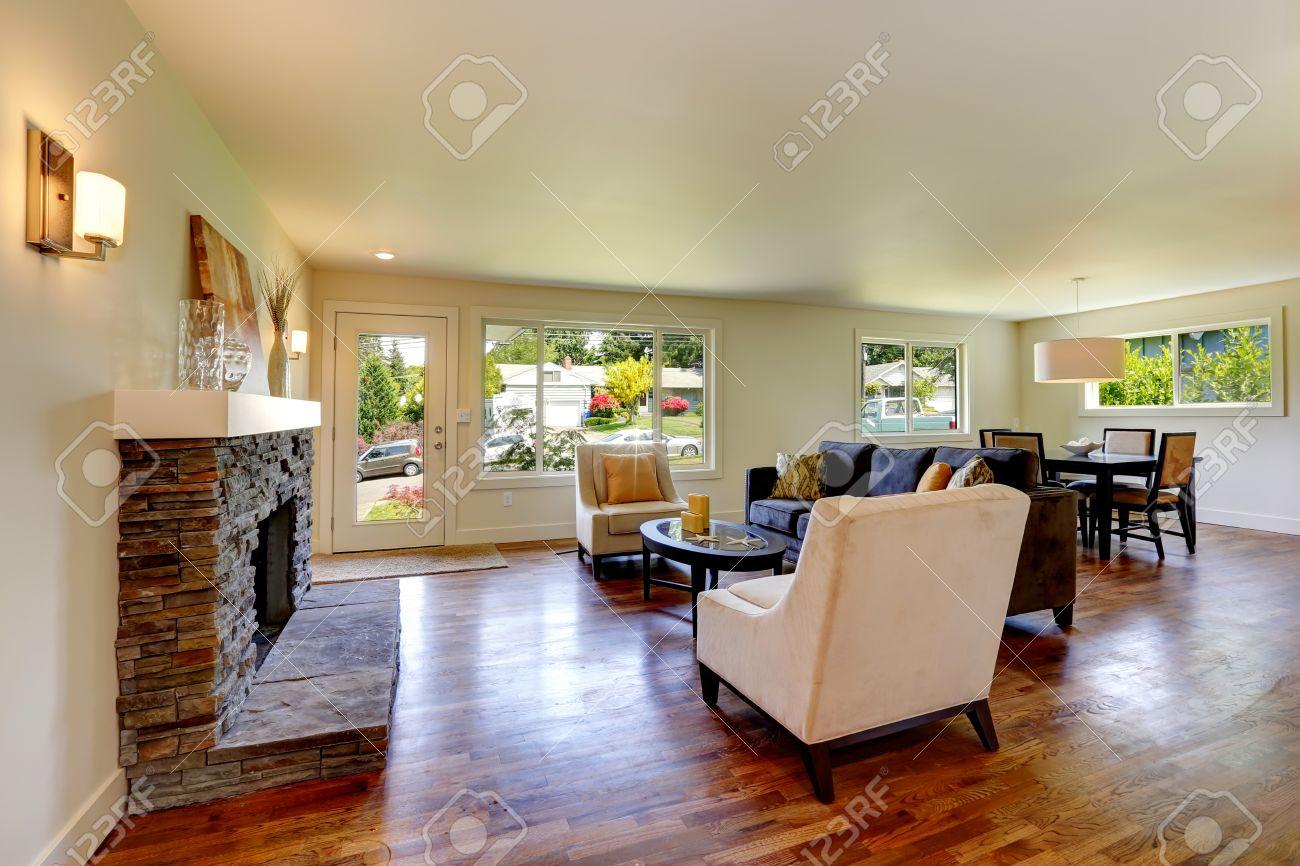 Woonkamer met stenen achtergrond open haard, bank, stoelen en een ...