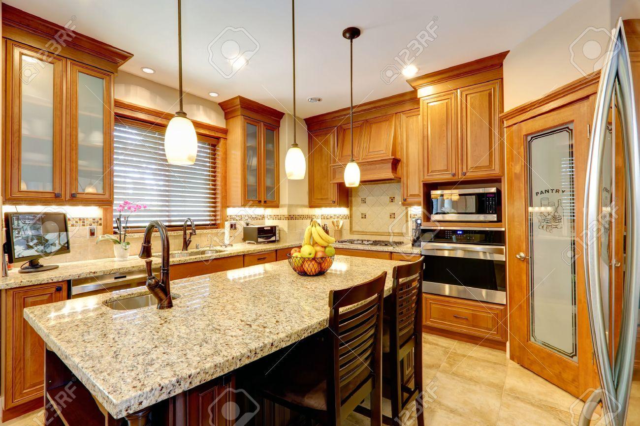 Cocina de lujo con muebles de color marrón claro, electrodomésticos de  acero, despensa, parte superior de la isla mostrador de mármol