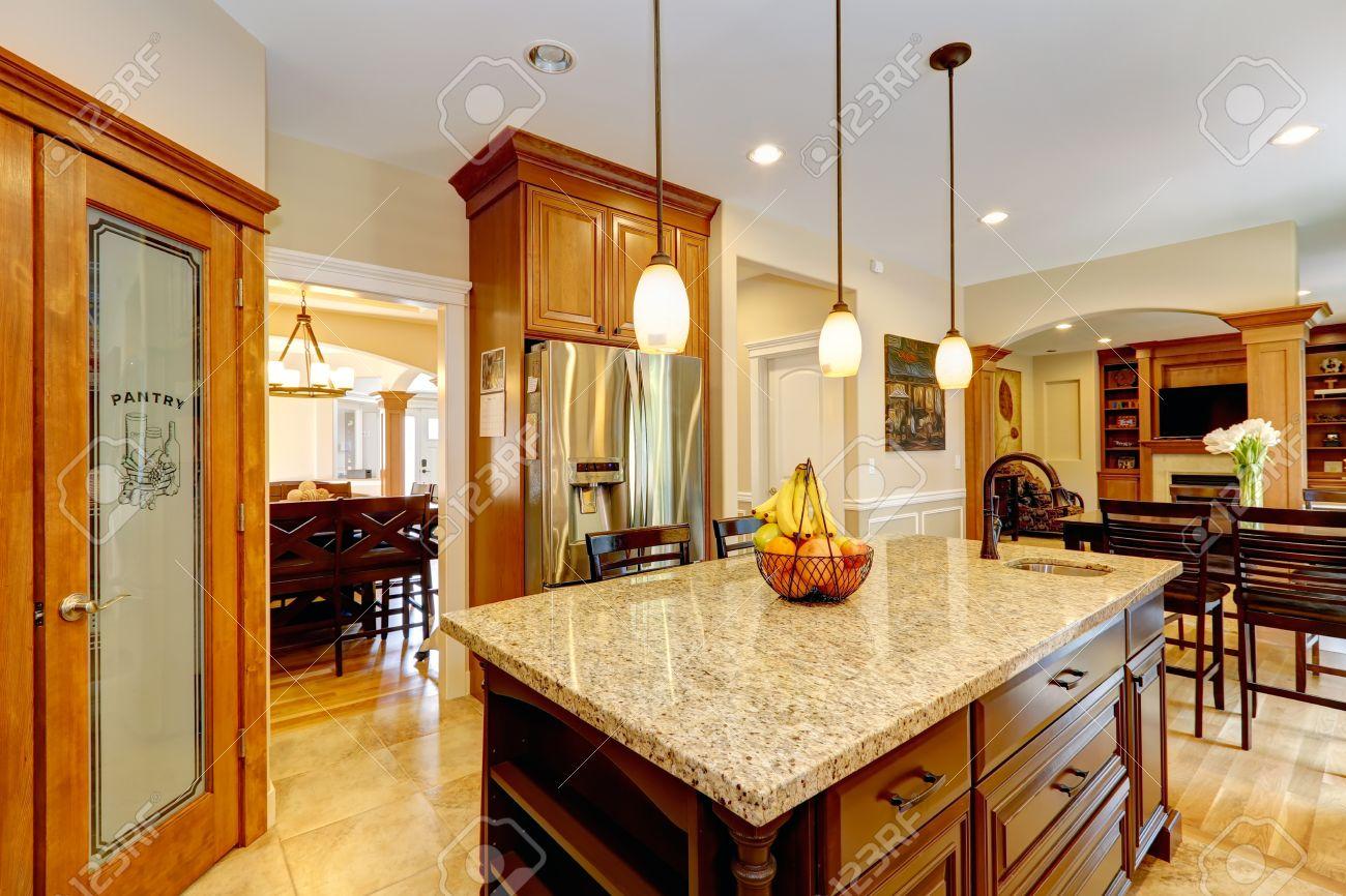 Luxe keuken met lichtbruin kasten, stalen apparatuur, bijkeuken ...
