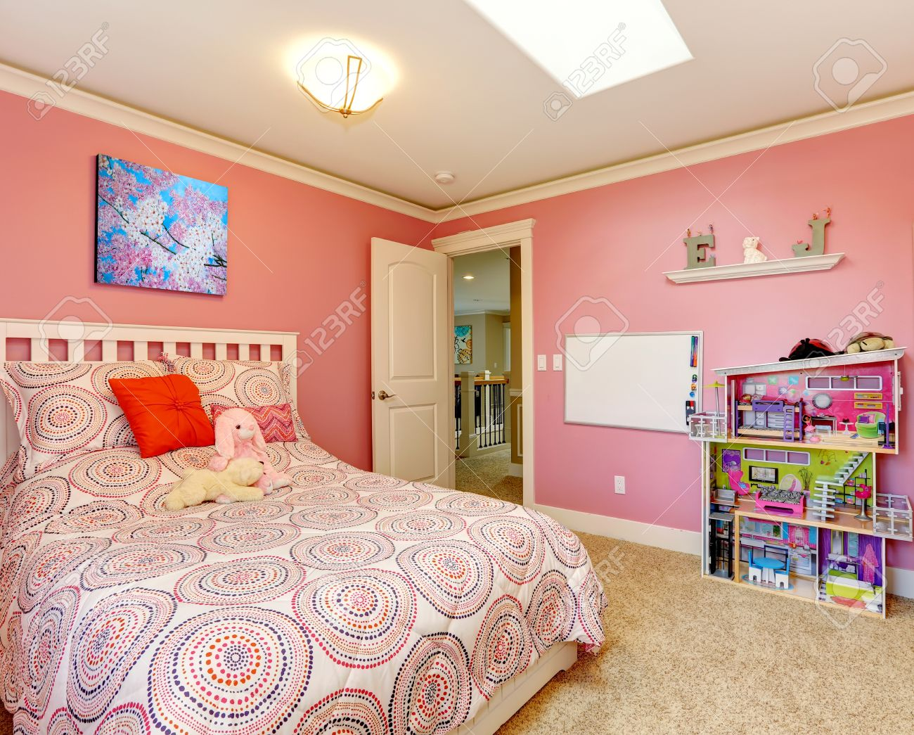 Gentle girls bedroom with white bed and pink walls View of board..