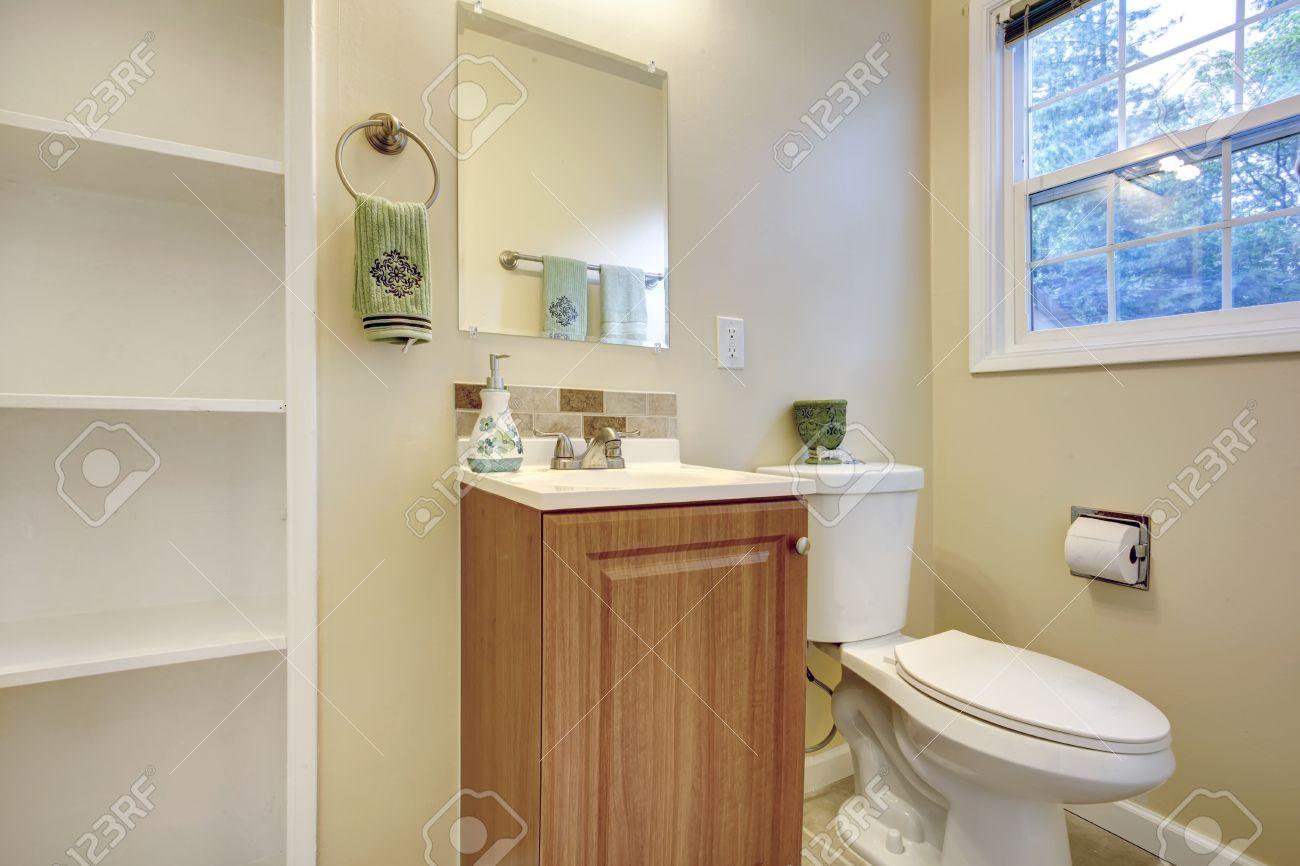 Helle Farbtöne Badezimmer Mit Französisch Fenster Mit Blick Auf  Waschbeckenschrank, WC Und Eingebauten Regalen Lizenzfreie