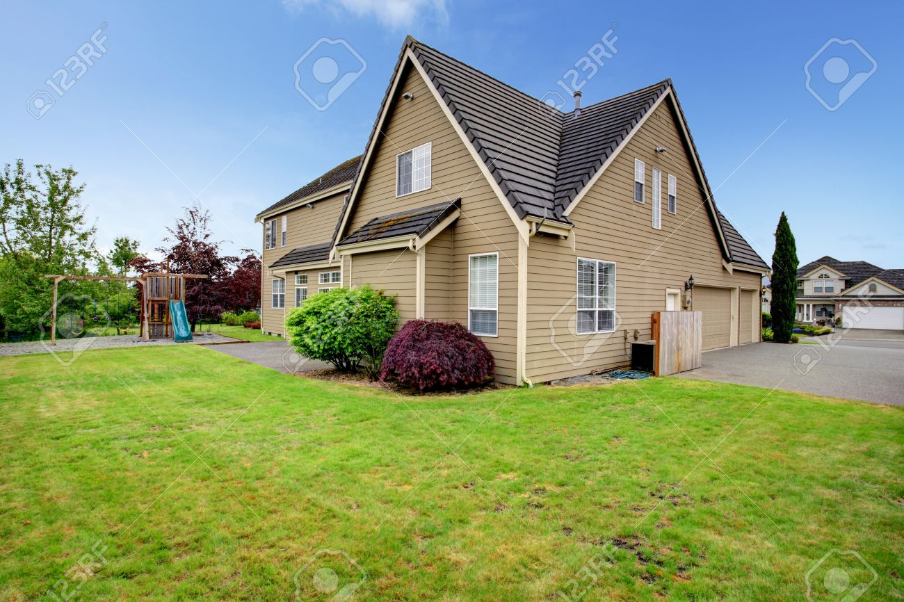big house with backyard playground green lawn garage and